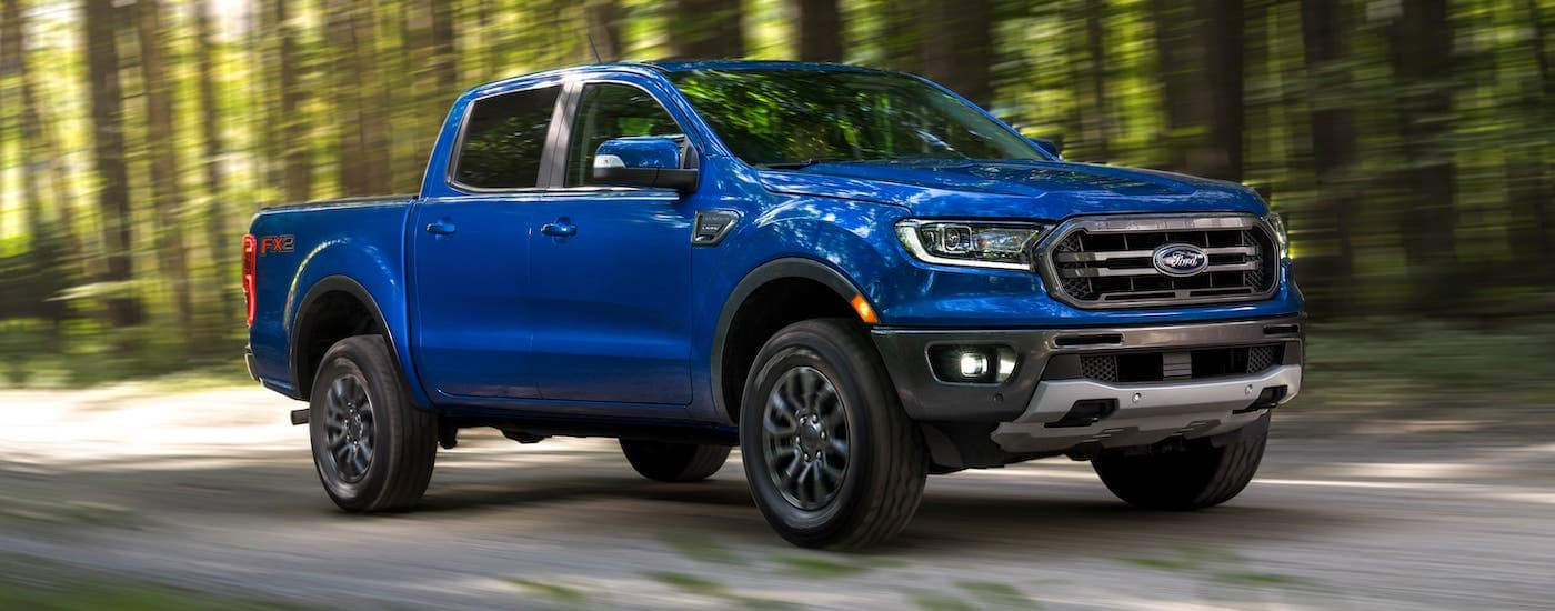 A newer used truck for sale here in Albany, a blue 2019 Ford Ranger Lariat is driving on a woodland road.