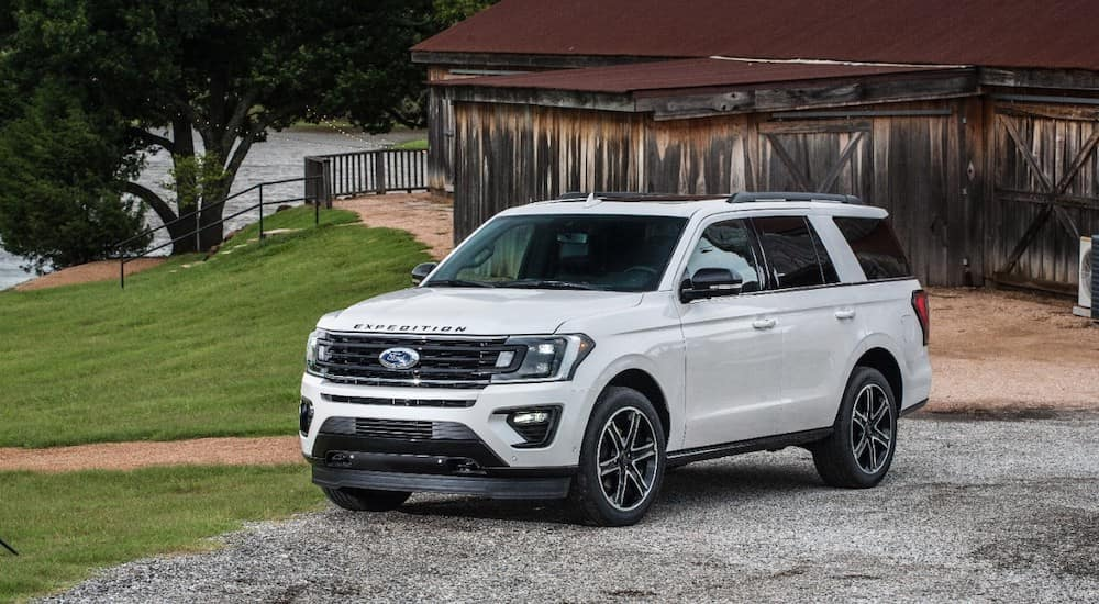 White 2019 Ford Expedition SUV parked in front of a brown building with a pond in the background