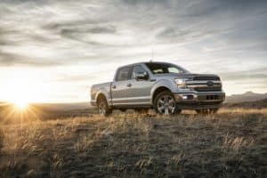 Gray 2018 Ford F-150 pick-up truck with cab in field with sunrise