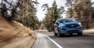 Blue 2019 Ford Edge ST SUV driving around a bend surrounded by trees during the day on a back road