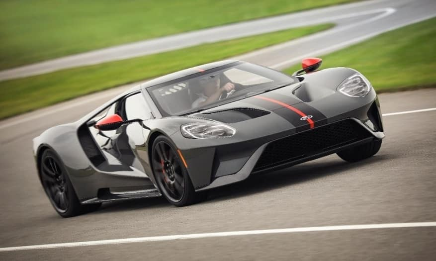 Gray 2019 Ford GT Carbon Series with a black and red racing stripe on the hood being driven by a man around a turn of a race track