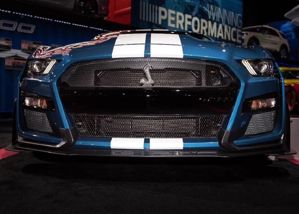 Front end closeup of a blue 2020 Ford Mustang Shelby GT500 with white racing stripes on the hood and chrome Shelby Cobra ornament on the grille displayed at the North American International Auto Show