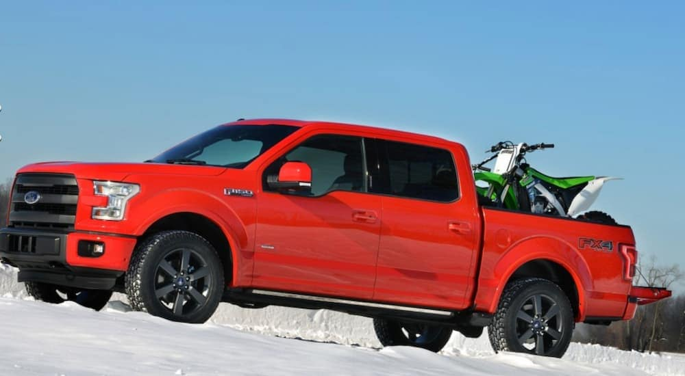 A red 2015 Ford F-150, popular at a local used car dealer near you, is parked on snow in Albany, NY.