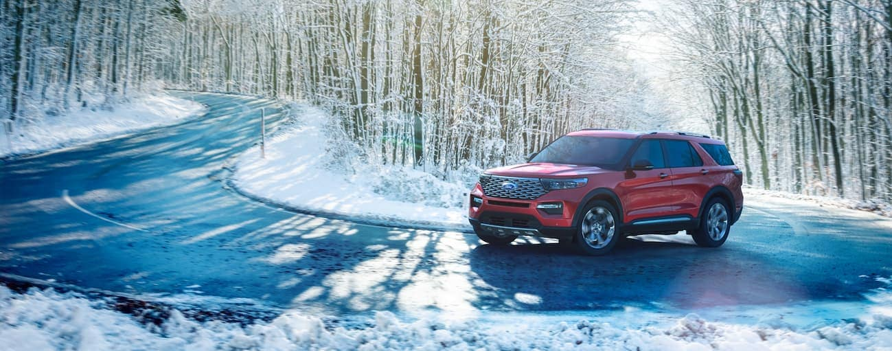 A red 2020 Ford Explorer is driving on a snowy road near Albany, NY.