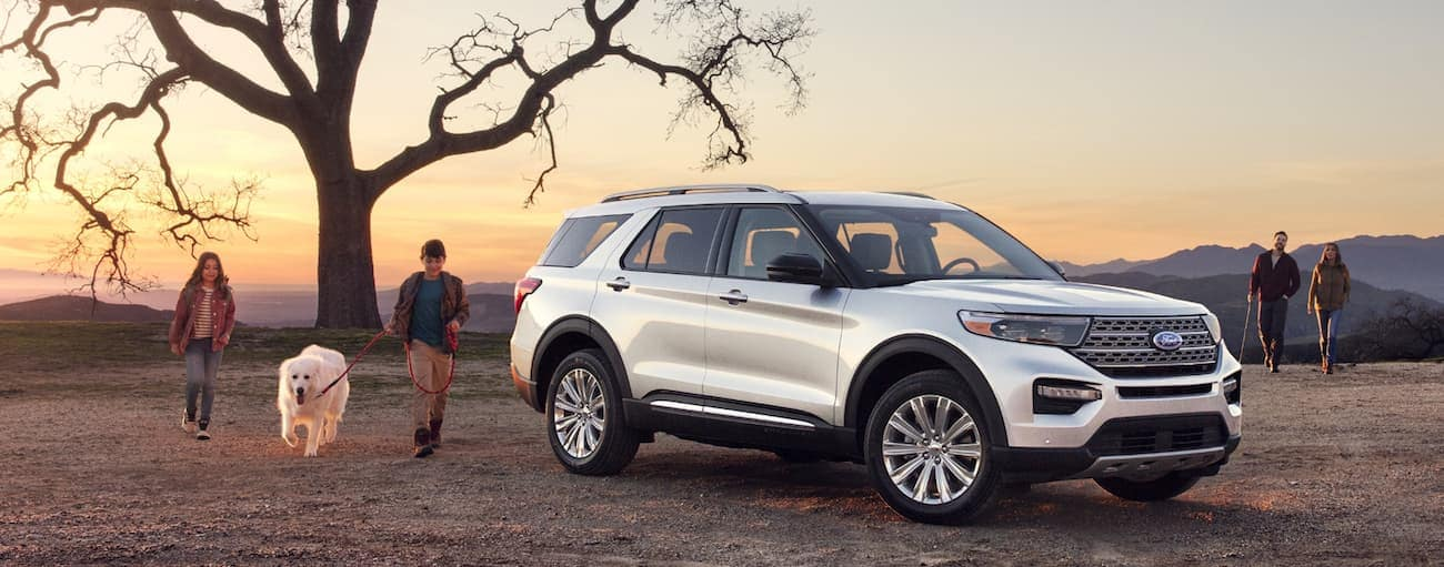 A white 2020 Ford Explorer is parked on a hill near Albany, NY while a family and their dog play around it.