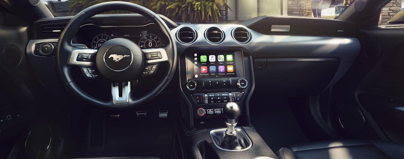 The front black leather interior of a 2020 Ford Mustang is shown.