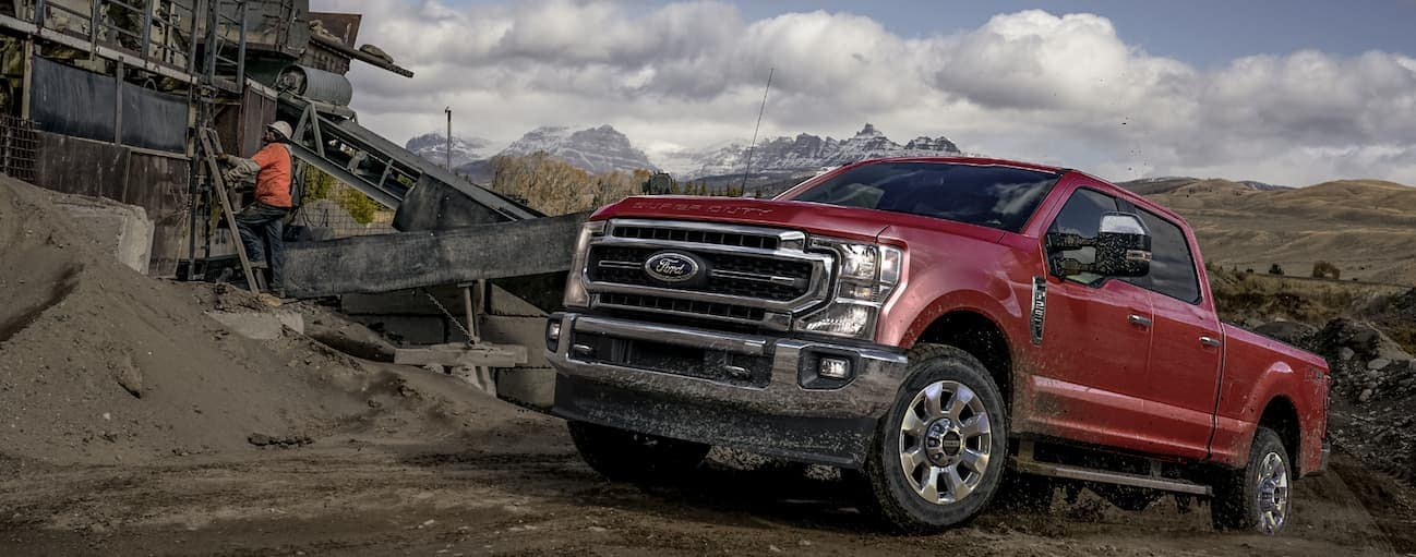 A red 2020 Ford Super Duty is parked on a dirt hill while men work next to it.