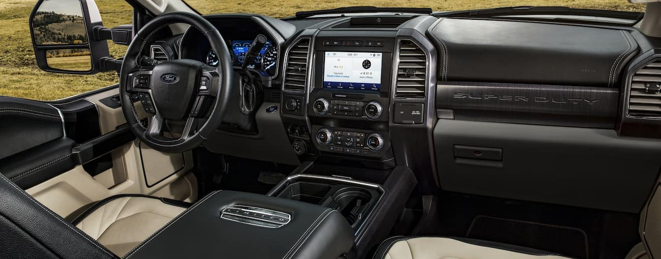The front interior of a 2020 Ford Super Duty with black and tan leather interior is shown.