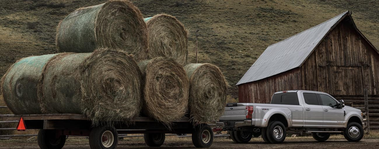 A silver 2020 Ford Super Duty is towing a large trailer with hay bails on it near Albany, NY.