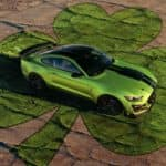 Lime green 2020 Mustang parked on top of a green clover painted on stone