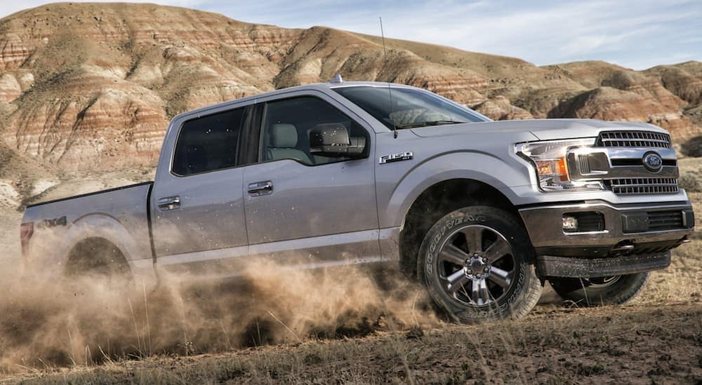 A silver 2020 Ford F-150 is driving through the dirt with a dust cloud.