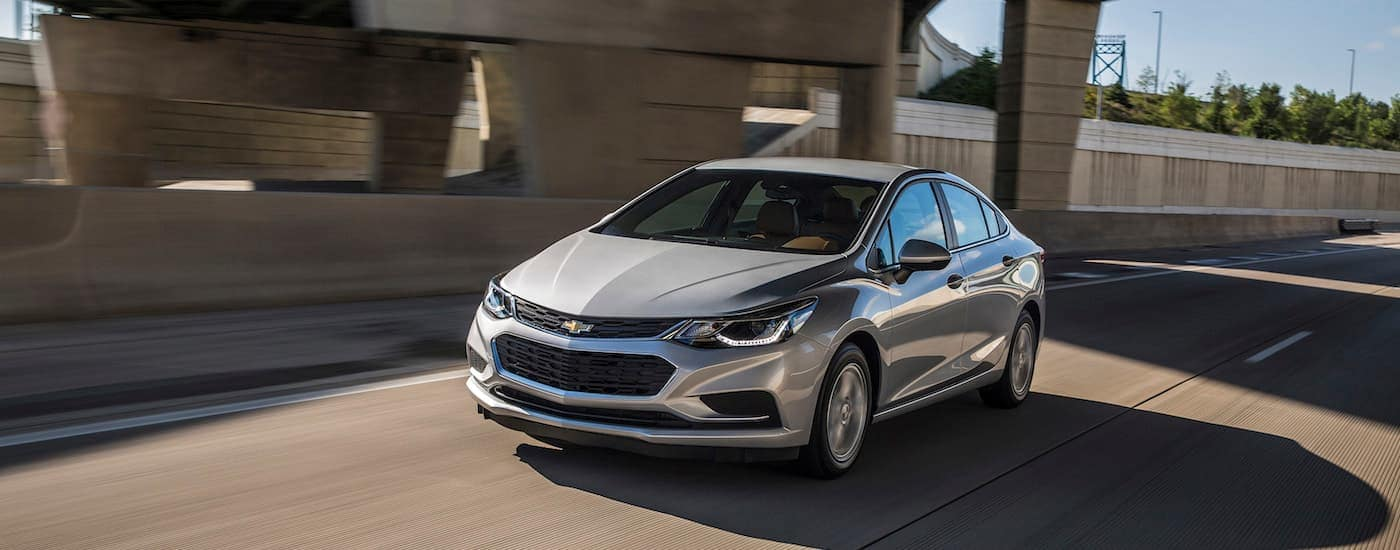 A silver 2017 Chevy Cruze, a car you may find when searching 'used car dealer near me', is driving on a highway near Albany, NY.