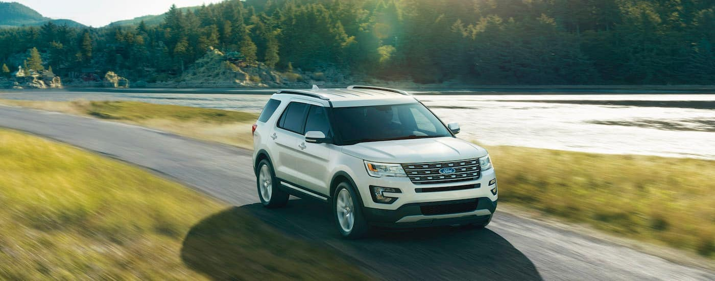 A white 2016 Ford Explorer is driving along a river.