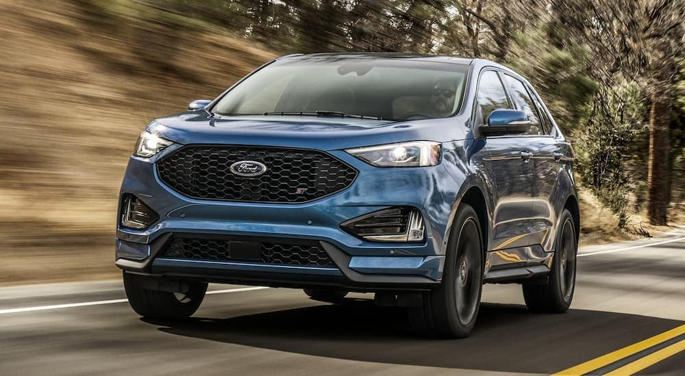 A blue 2020 Ford Edge is driving with a blurred background after leaving a Ford dealership in Albany, NY.