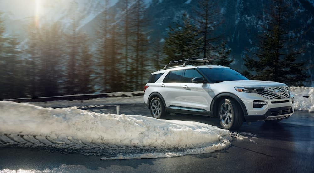 A white 2020 Ford Explorer, popular among 4WD vehicles at Ford Dealerships in Albany, NY, is driving on a winter day.