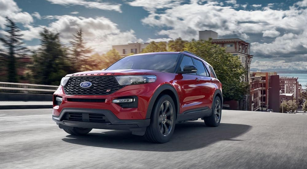 A red 2020 Ford Explorer is driving on a city street.