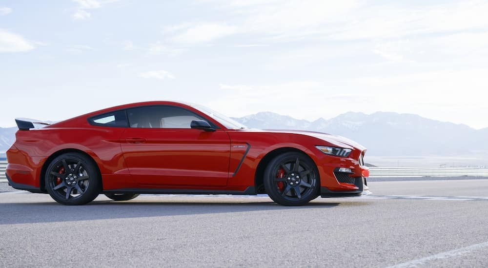 A red 2020 Ford Mustang GT350 is parked facing a race track.