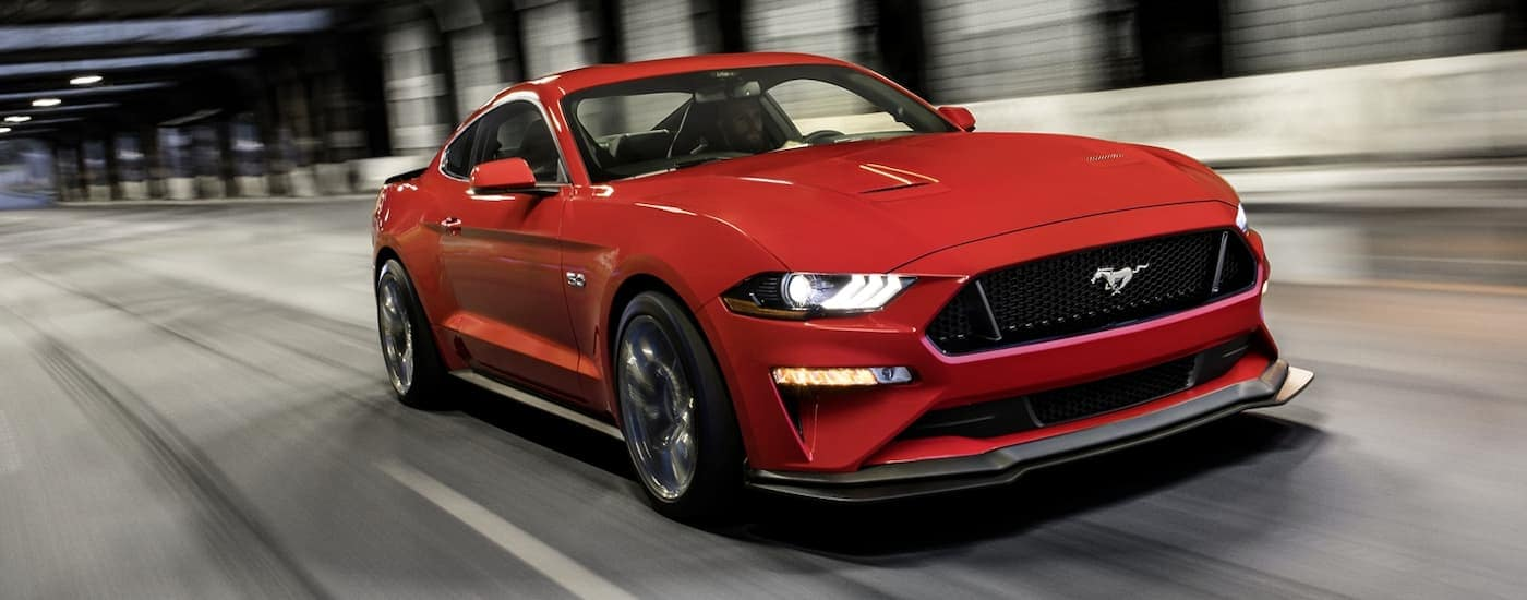 A red 2020 Ford Mustang is driving in a tunnel.