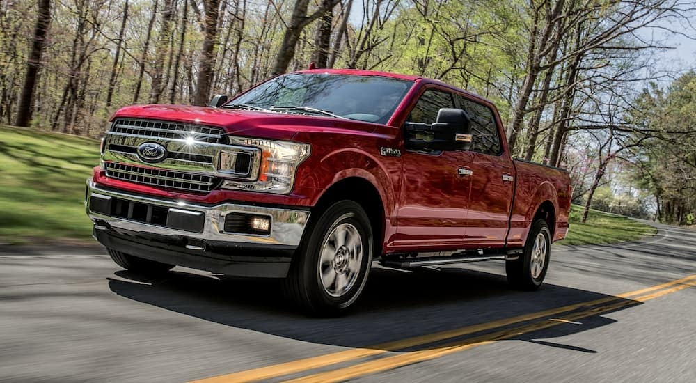 A red 2020 Ford F-150, popular among Ford trucks, is driving on a tree-lined road near Albany, NY.