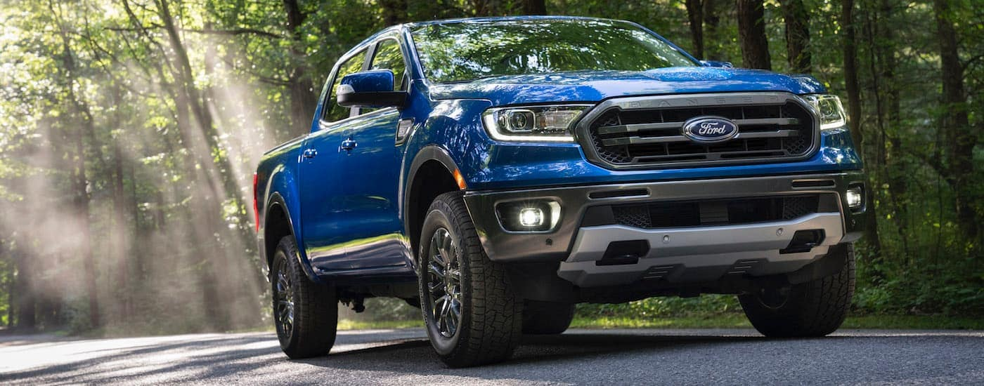 A blue 2020 Ford Ranger is driving on a tree-lined road.