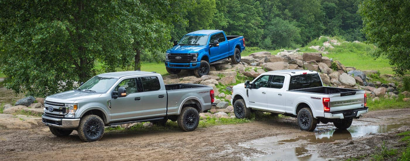 The 2020 Ford Super Duty trio are shown in silver, white, and blue on a muddy trail.