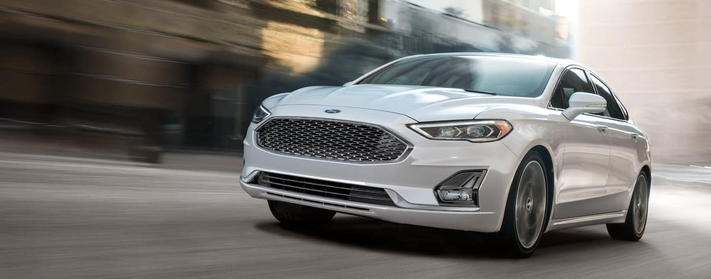 A white 2020 Ford Fusion, a vehicle that you could find at local car dealers, is driving on a city street in Albany, NY.