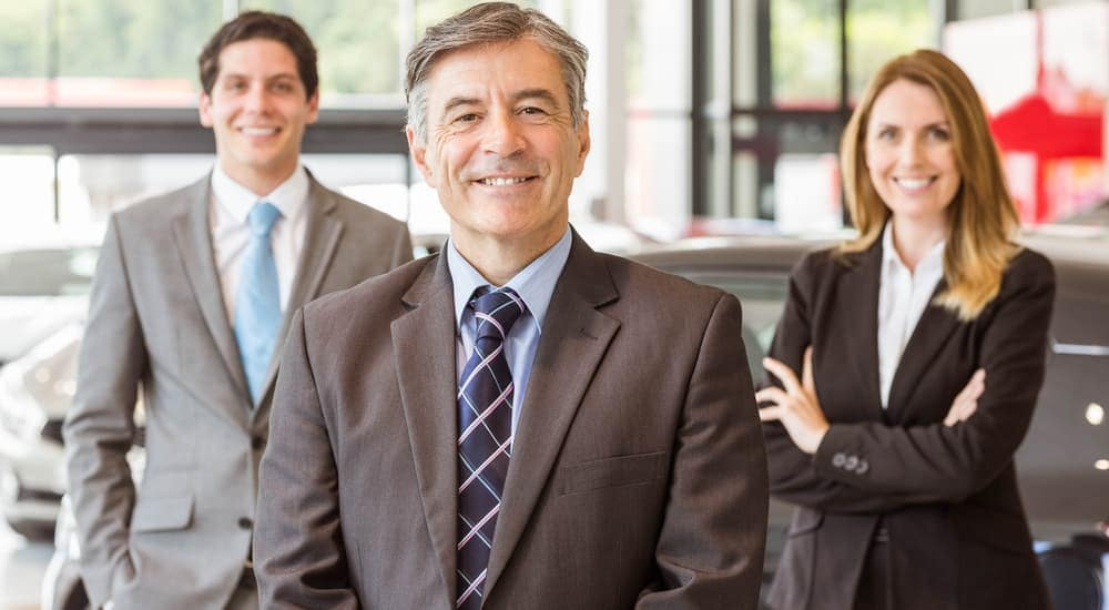 Three smiling sales people are standing in a local car dealers showroom in Albany, NY.