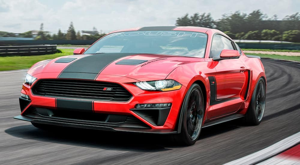 A red and black Ford Mustang is equipped with Roush racing performance parts while racing on a racetrack.