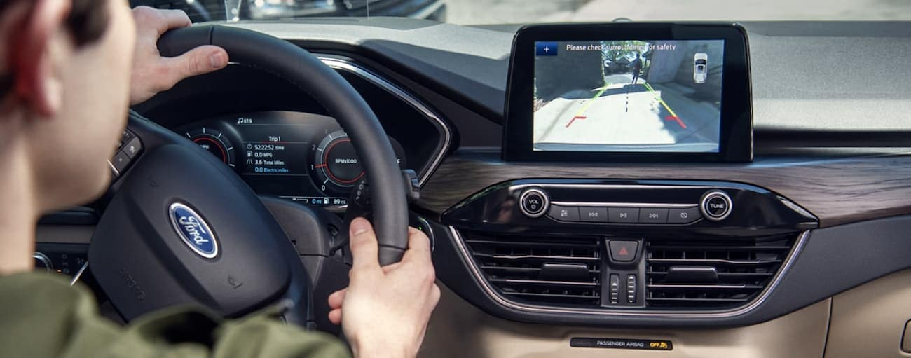 A man is looking at the back up camera view on his infotainment screen in the 2020 Ford Escape.