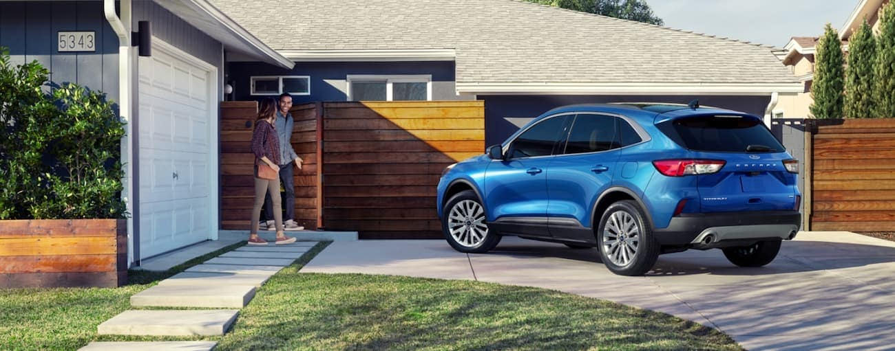 A couple is walking to their blue 2020 Ford Escape outside their Albany, NY home.