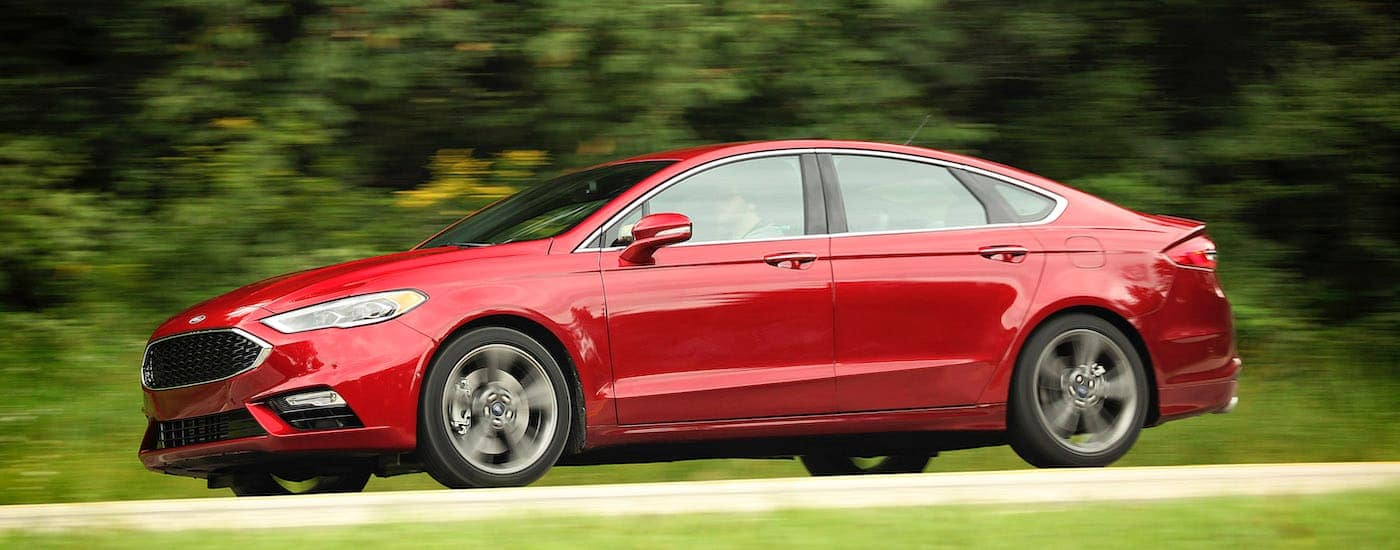 A red 2017 Ford Fusion is driving on a tree-lined road.
