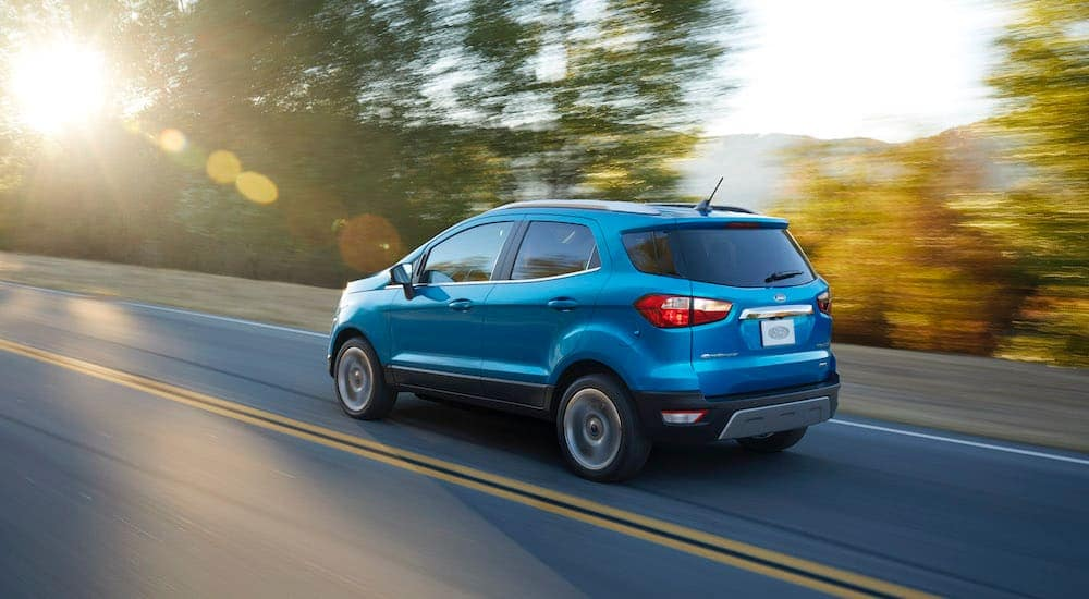 A blue 2018 Ford Ecosport is driving on a sunny road near Albany, NY.