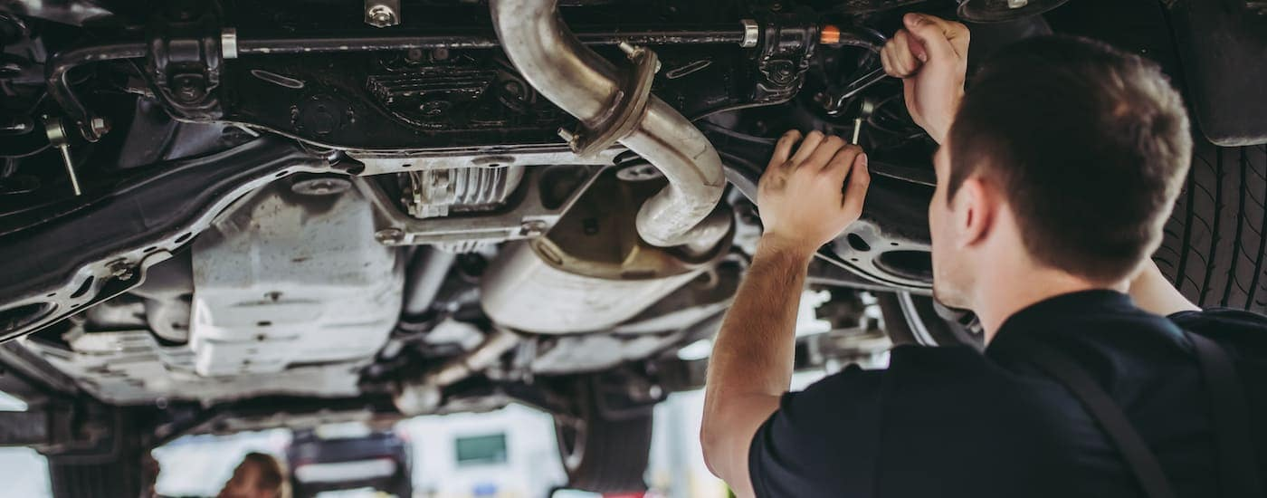 A mechanic is working under a vehicle at a used car dealer in Albany, NY.