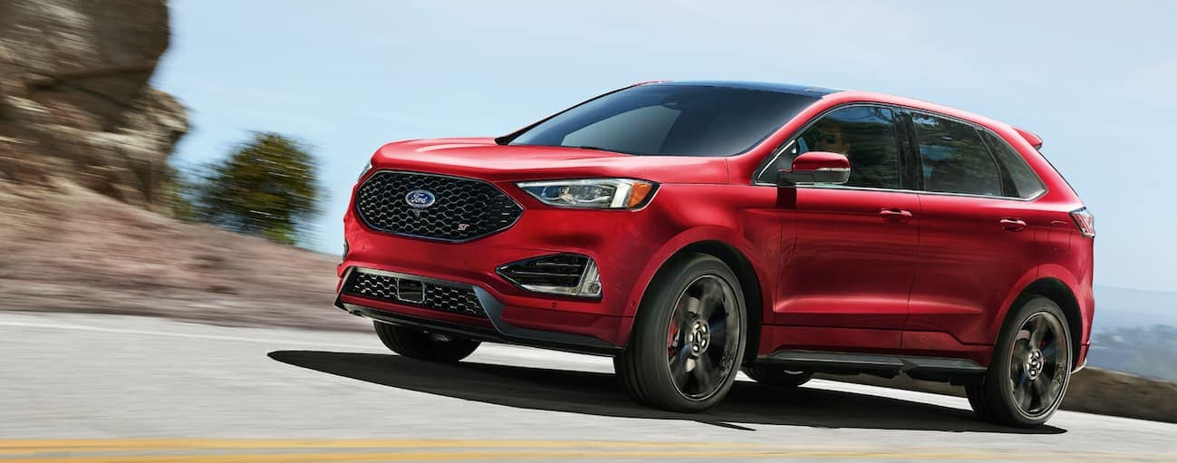 A red 2020 Ford Edge ST is driving on a highway outside of Albany, NY.