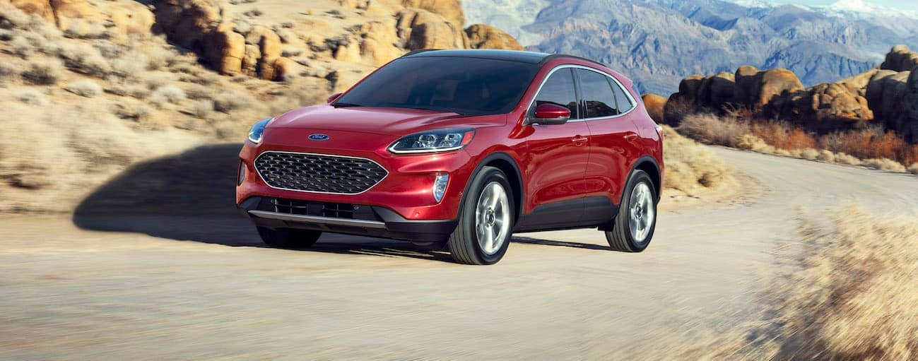 A red 2020 Ford Escape is driving up a dirt hill with mountains in the background.