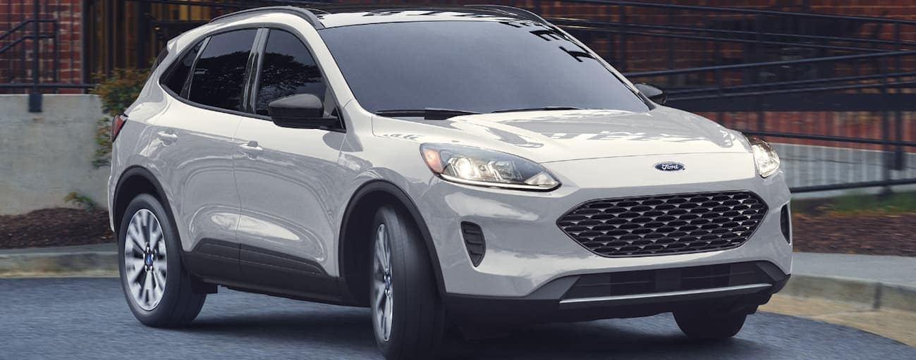A white 2020 Ford Escape, which wins when comparing the 2020 Ford Escape vs 2020 Chevy Equinox, is driving out of a restaurant's parking lot near Cincinnati, OH.