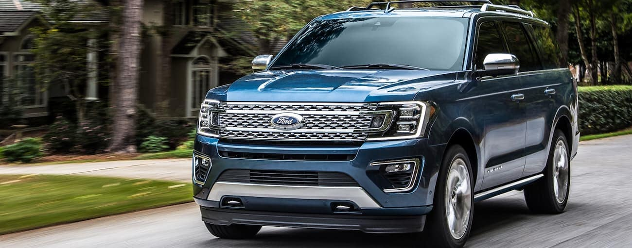 A blue 2020 Ford Expedition is driving on a road passing large houses near Albany, NY.