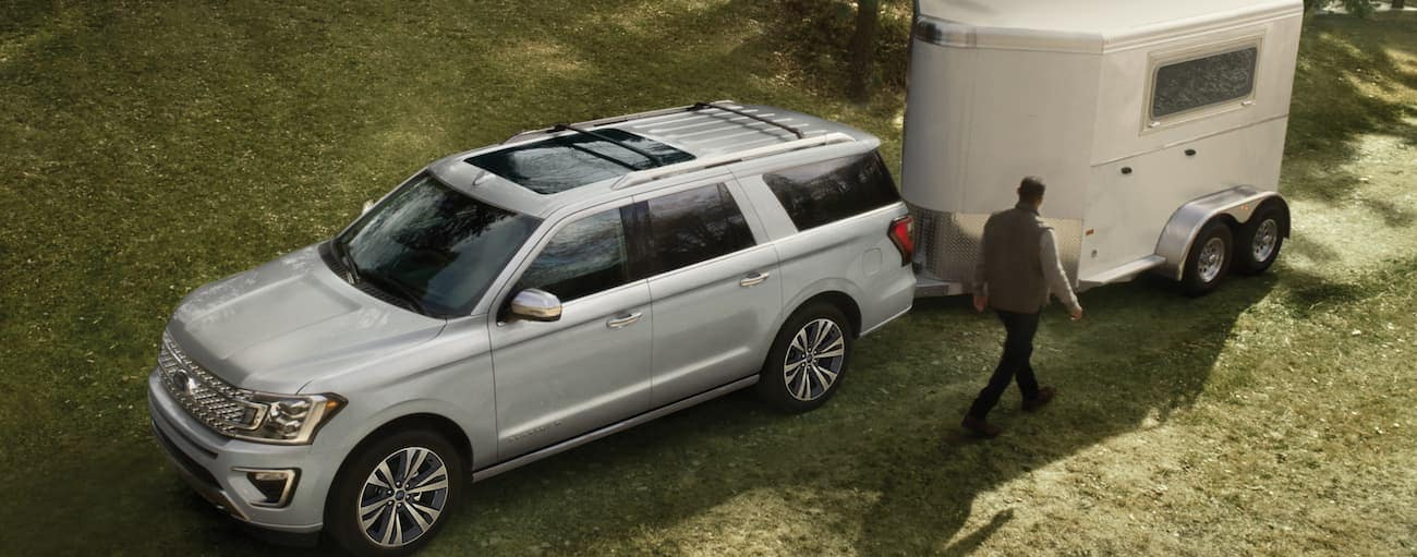 A silver 2020 Ford Expedition is parked in grass with a horse trailer attached to it.
