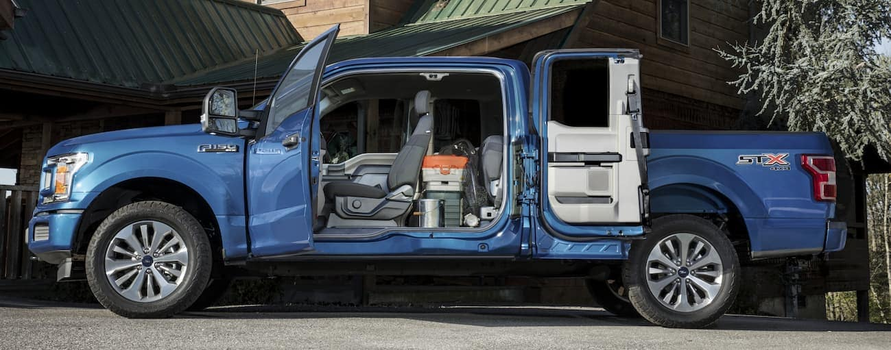 A blue 2020 Ford F-150 is parked outside an Albany, NY home's driveway with the doors open showing the interior.