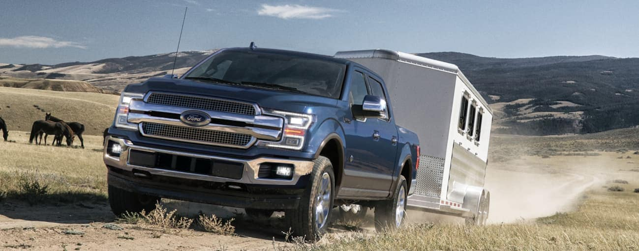 A dark blue 2020 Ford F-150 is towing a large horse trailer on a dirt road.