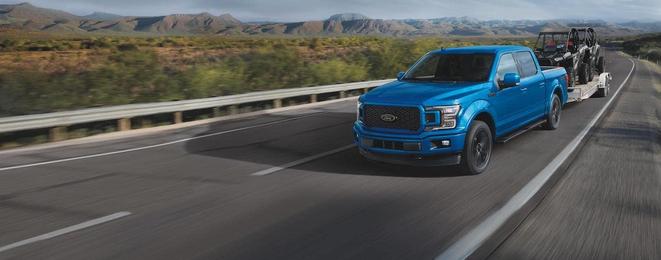 A blue 2020 Ford F-150 is towing 2 side by sides on a trailer outside of Albany, NY.