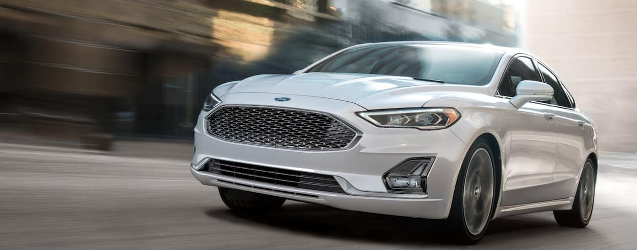 A white 2020 Ford Fusion is driving on a city street near Albany, NY.