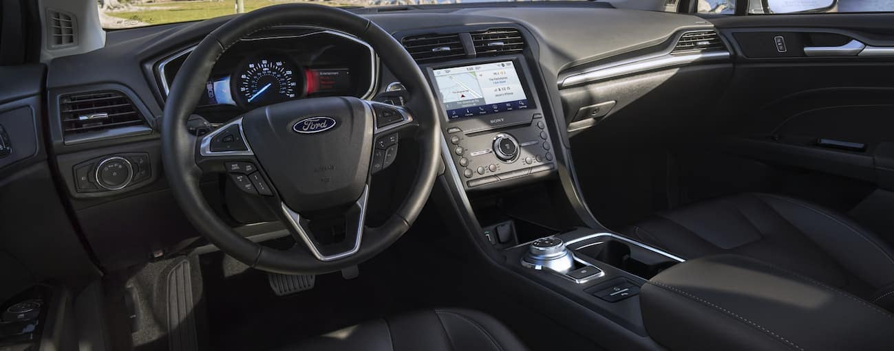 The front black leather interior of a 2020 Ford Fusion.