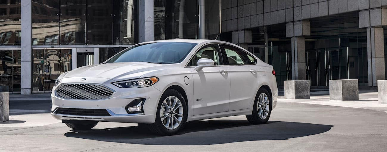A white 2020 Ford Fusion Plug-In Hybrid is parked in front of a glass building near Albany, NY.