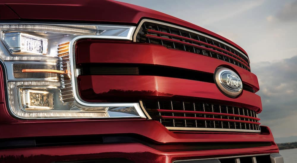 The grille of a red 2020 Ford F-150 is shown in a close up.