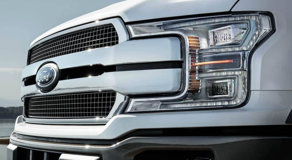 A close up of a white 2019 Ford F-150's grille is shown.