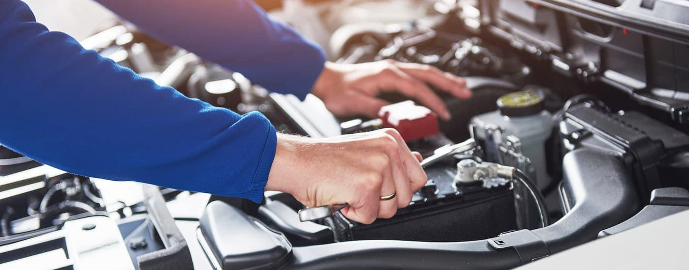 A close up is shown of a mechanic working under the hood of a car at one of the Ford dealership locations in Albany, NY.