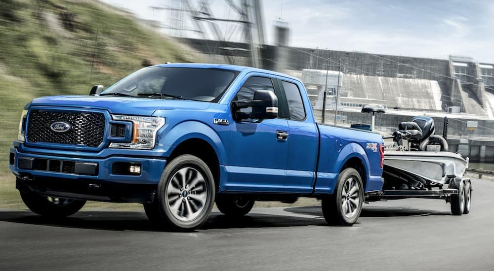 A blue 2020 Ford F-150, a popular truck at local Ford dealership locations in Albany, NY, is towing a boat.
