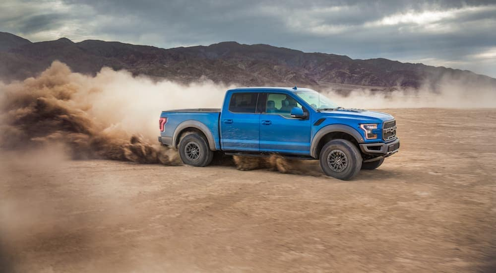 A blue 2020 Ford Raptor is driving through a dirt pit with a dirt cloud behind.