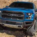 A blue 2020 Ford Raptor, a popular option among Ford trucks for sale in Albany, NY, is crawling up a rock hill.